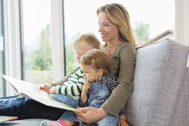 Мать и двое маленьких детей сидят на диване и читают книгу — стоковое фото