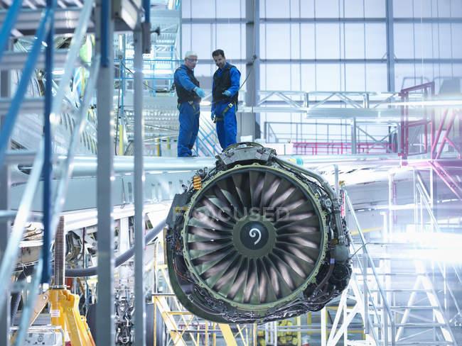Инженеры самолетов, стоящие на крыле с реактивным двигателем на заводе по обслуживанию самолетов — стоковое фото