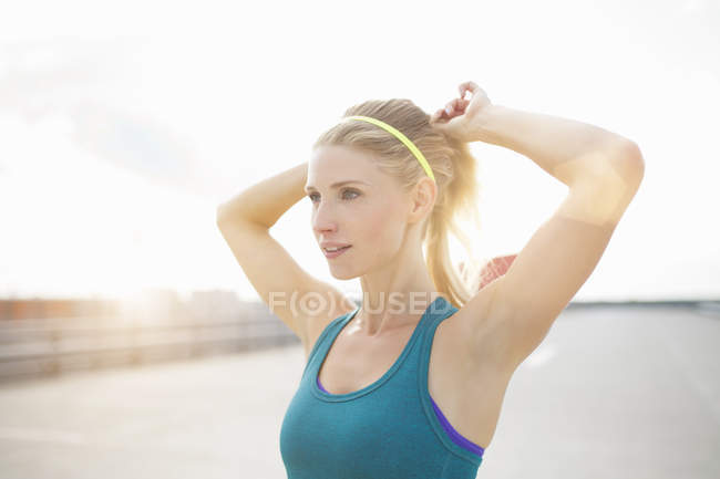 Young woman adjusting ponytail — Stock Photo