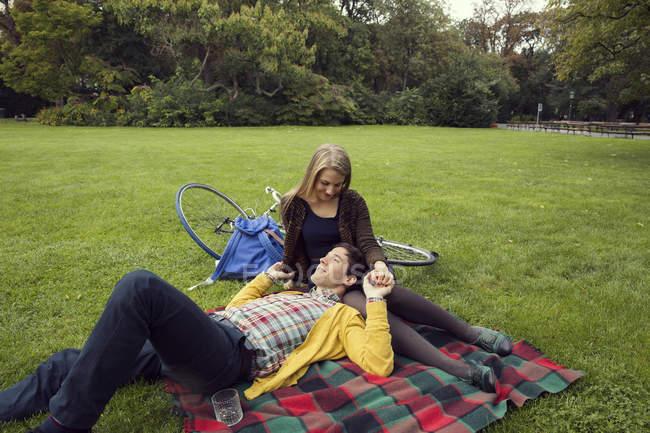 Junges Paar hält Hände auf Picknickdecke im Park — Stockfoto