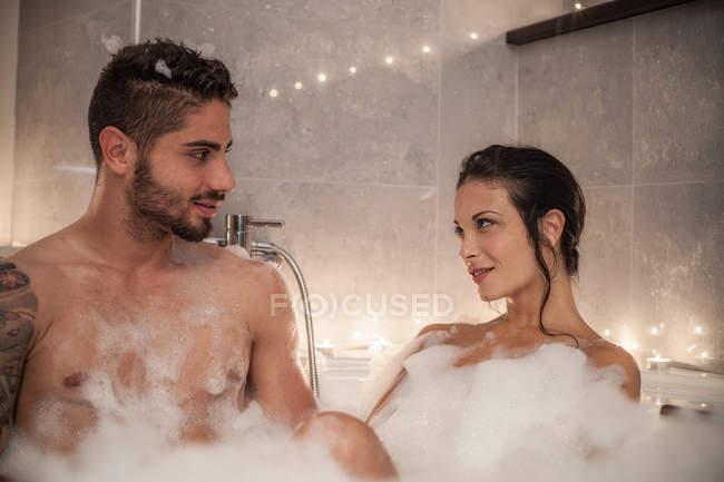 Jovem casal olhando um para o outro no banho de bolhas — Fotografia de Stock