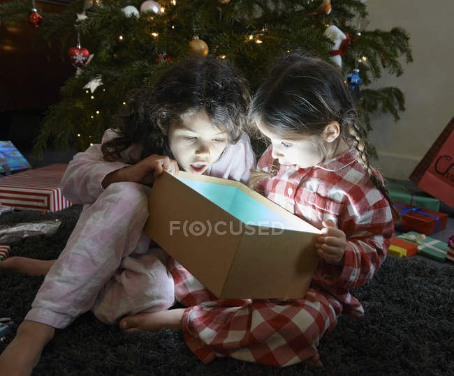 Two kids open mouthed on unwrapping glowing Christmas gift box — Stock Photo