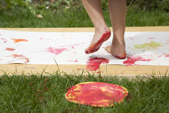 Child feet covered in paint on paper outdoors — Stock Photo