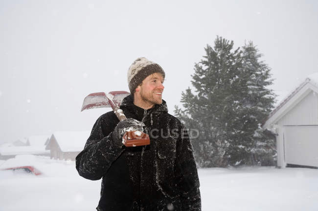 Man standing with snow shovel on shoulder — Stock Photo