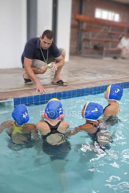 Четыре школьницы играют в водное поло, слушая учителя у бассейна — стоковое фото