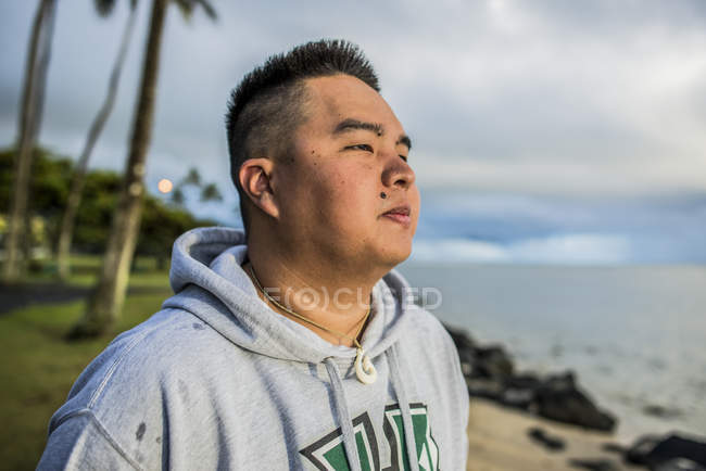 Hombre joven mirando al amanecer desde Kaaawa beach, Oahu, Hawaii, Usa - foto de stock