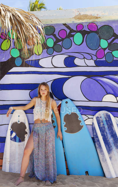 Portrait of young woman leaning against surfboard beach hut, Dominican Republic, The Caribbean — Stock Photo