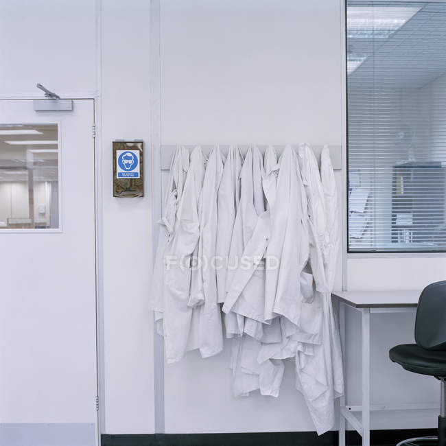 Lab coats hanging on hooks in laboratory — Stock Photo