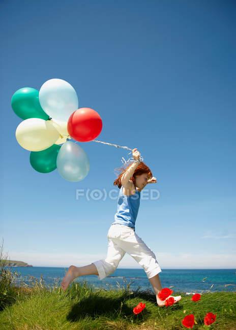 Молодая девушка бежит с воздушными шарами — стоковое фото