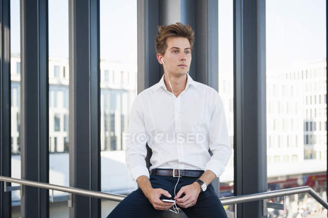 Young businessman wearing earphones while sitting on table — Stock Photo