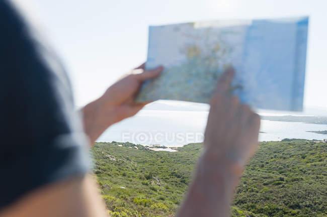 Zugeschnittenen Überblick mans Hände halten Karte an Küste, Sardinien, Italien — Stockfoto