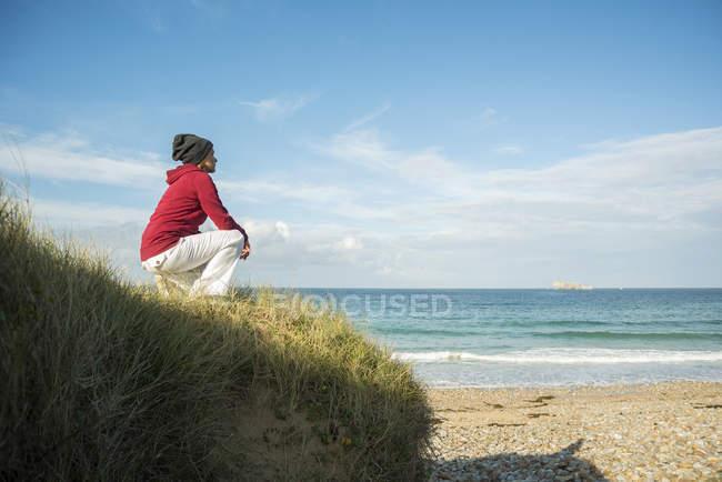 Femme mûre accroupie et regardant l'eau de mer, Camaret-sur-mer, Bretagne, France — Photo de stock