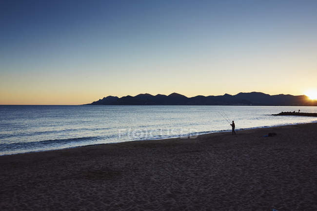 Tranquil scene of fisherman on beach of French Riviera, Cannes, France — Stock Photo