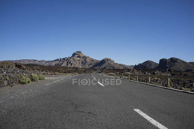 Empty road with mountains on background — Stock Photo