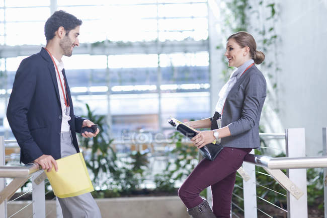 Businessman and businesswoman chatting in conference centre atrium — Foto stock