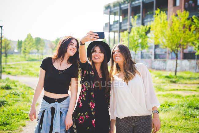 Три молодих жінок позують для смартфона селфі в парку — стокове фото