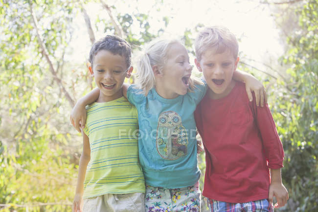 Three children having fun in garden — стокове фото