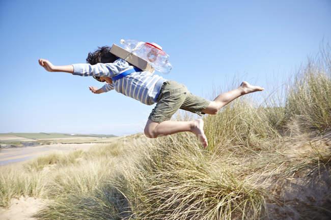 Молода хлопчика на пляжі, носіння костюмований, стрибаючи в повітрі — стокове фото