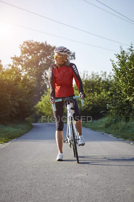 Reife Radfahrer mit Renn-Fahrrad auf Landstraße — Stockfoto