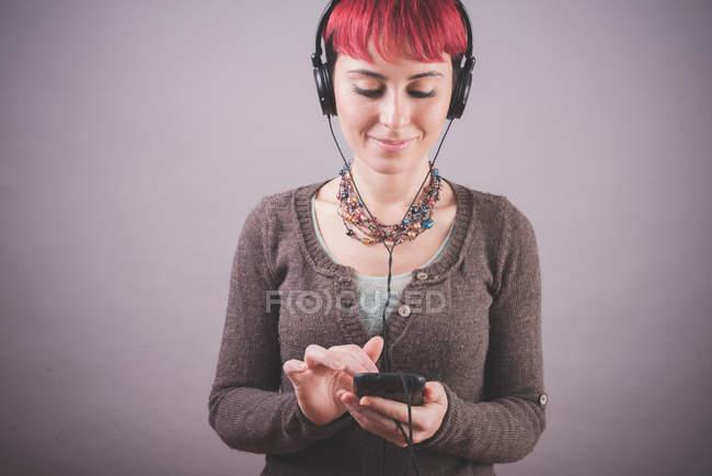 Studio-Porträt der jungen Frau mit kurzen rosa Haaren Auswahl Musik auf smartphone — Stockfoto