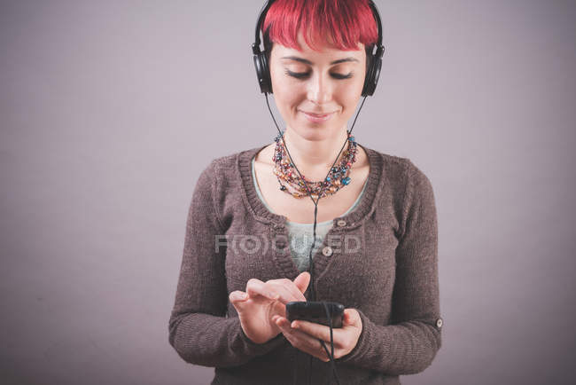 Studio portrait of young woman with short pink hair choosing music on smartphone — Stock Photo