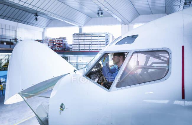 Инженеры работают в кабине самолета на авиаремонтном заводе — стоковое фото