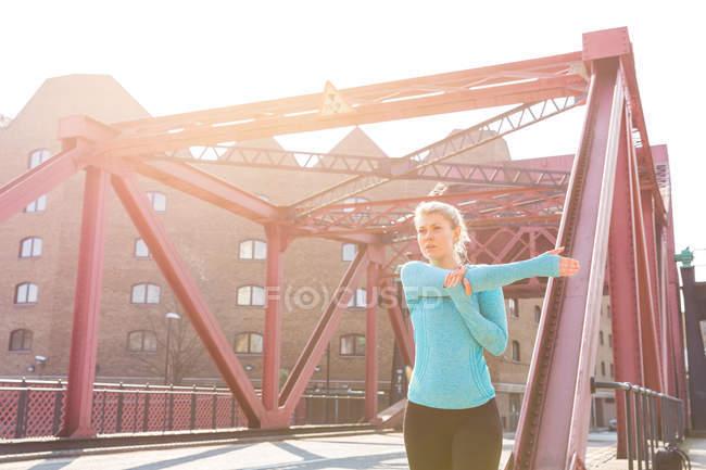 Молода жінка, що здійснює на відкритому повітрі, розтягування — стокове фото