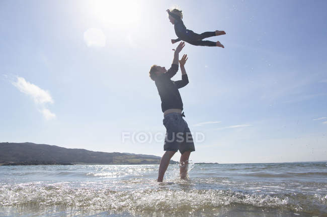 Padre che lancia il figlio in aria sulla spiaggia, Loch Eishort, Isola di Skye, Ebridi, Scozia — Foto stock