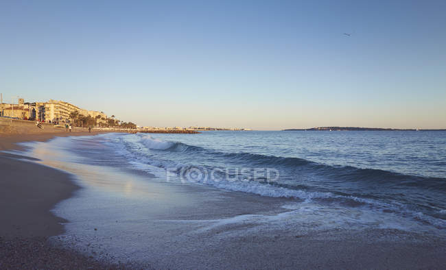 Scenic sandy beach with hotel buildings and people in background, French Riviera, Cannes, France — Stock Photo