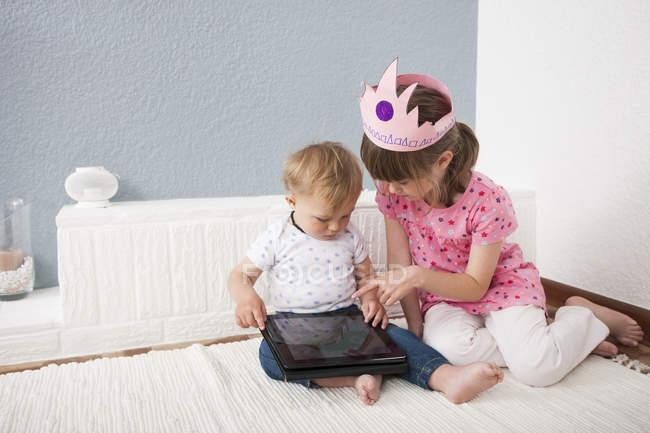 Девочка наблюдает за малышом, играющим в цифровой планшет — стоковое фото