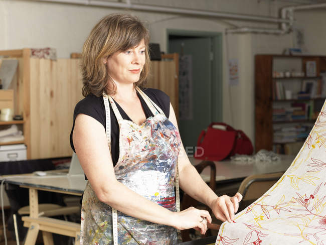 Woman checking fabric in hand-printed textile workshop — Stock Photo