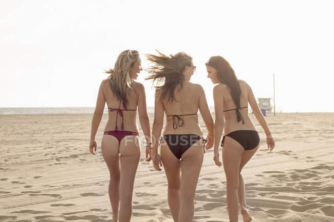 Rear view of three young women strolling on beach — Fotografia de Stock