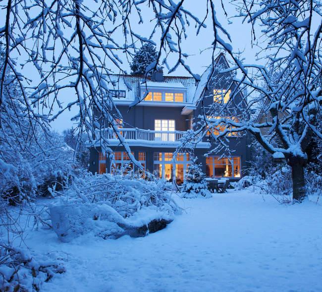 Casa illuminata e cortile coperto di neve — Foto stock