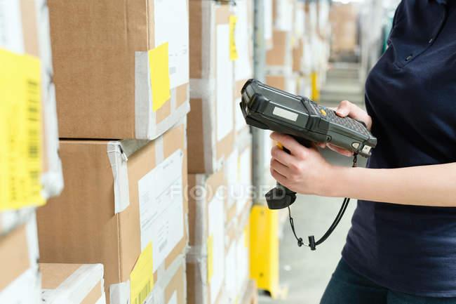 Vista recortada de trabajador de almacén utilizando el escáner de código de barras en la caja en el almacén de distribución - foto de stock