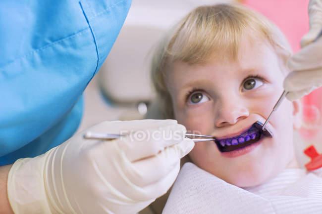Fille avec plaque révélant comprimé sur les dents ayant un examen dentaire — Photo de stock