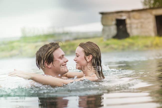 Romantic young couple splashing in Secret Lagoon hot spring (Gamla Laugin), Fludir, Iceland — Stock Photo
