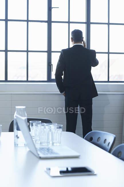 Задний вид делового человека в чате на смартфоне в конференц-зале — стоковое фото