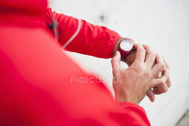 Cropped close up of young male runner checking smartwatch — Stock Photo