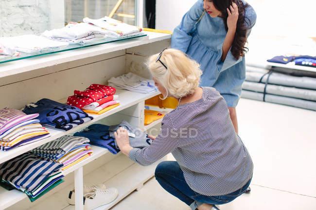 Frauen im Bekleidungsgeschäft Blick auf Preisschild auf t-shirts — Stockfoto