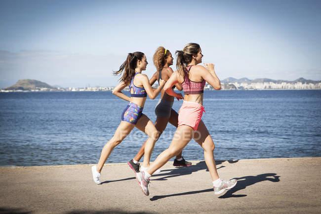 Three young women jogging on beach — Stock Photo