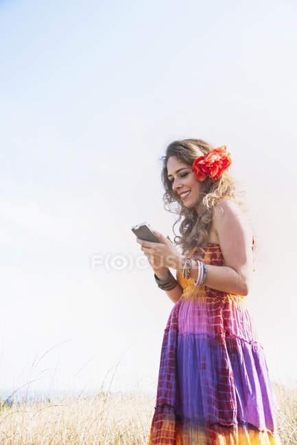 Metà donna adulta con fiore in capelli, utilizzando smartphone, all'aperto — Foto stock