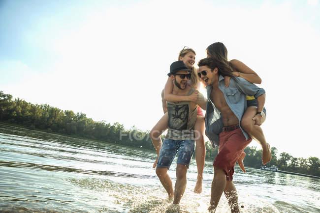 Junge Männer geben jungen Frauen Huckepack — Stockfoto