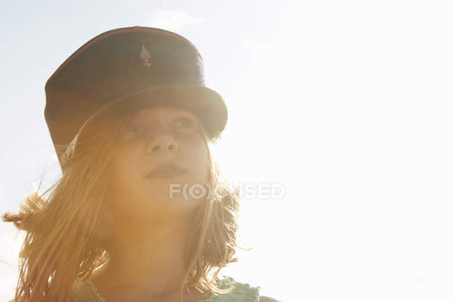 Portrait of girl in cap at sunlit coast — Stock Photo