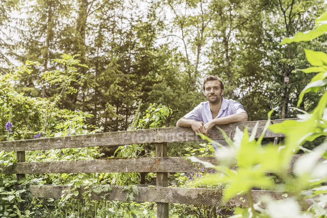 Portrait of mid adult man leaning on garden fence — Stock Photo