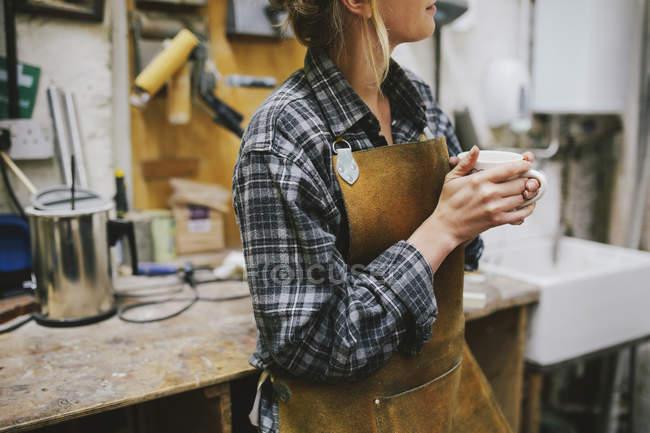 Junge Handwerkerin trinkt Kaffee in Pfeifenorgelwerkstatt — Stockfoto
