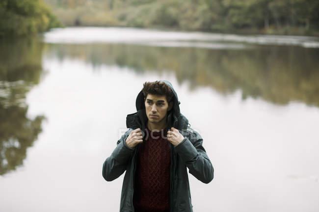 Junger Mann stehend Blick vom Ufer — Stockfoto