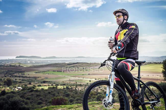 Masculino mountain biker com garrafa de água no caminho costeiro, Cagliari, Sardenha, Itália — Fotografia de Stock