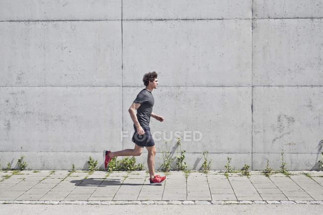 Young man running along on urban sidewalk — Stock Photo