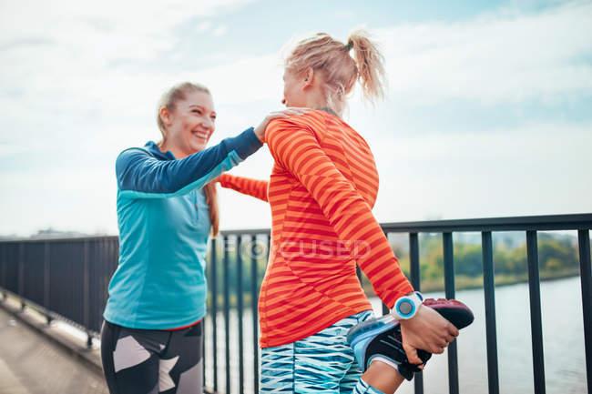 Dos corredoras haciendo ejercicio de calentamiento juntas en la pasarela - foto de stock