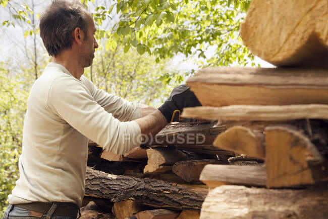 Man stacking cutted wood — Stock Photo